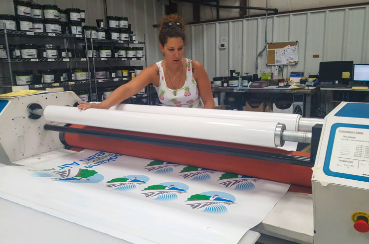 designer decal employee laminating a product
